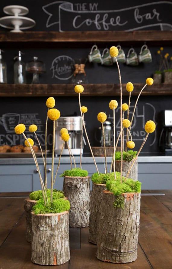 coole Bastelidee für DIY Deko mit kleinen baumstämmen, moos, und holzstäben mit gelben Pompons