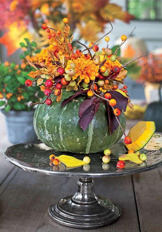 coole dekoideen mit DIY Vase aus grünem Kürbis auf silbernem tortenständer gefüllt mit orangen Blumen, herbstblättern und Beerenzweigen aus Baumwürger