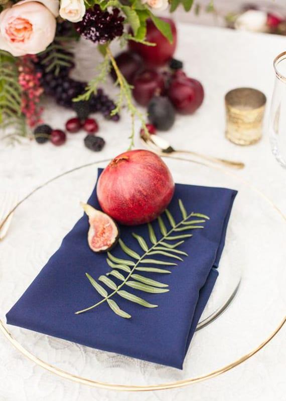 moderne herbstdeko tisch mit pflaumen,beerenzweigen und beeren, weißen platztellern mit dunkelblauen servietten, granatapfel und feige