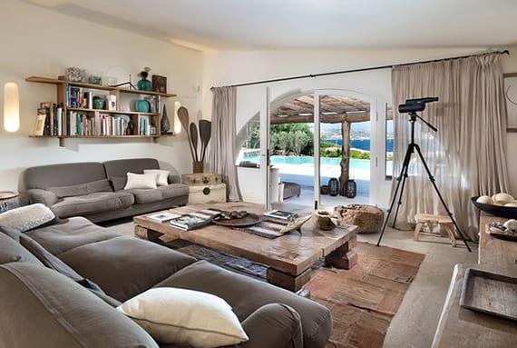 modernes wohnzimmer design im rustikalen stil mit betonboden,grauen sofas, regalen und couchtisch aus massivholz,gardinen grau,rustikale deko-accessoires und halbrundem gang zu überdachte terrasse mit pool