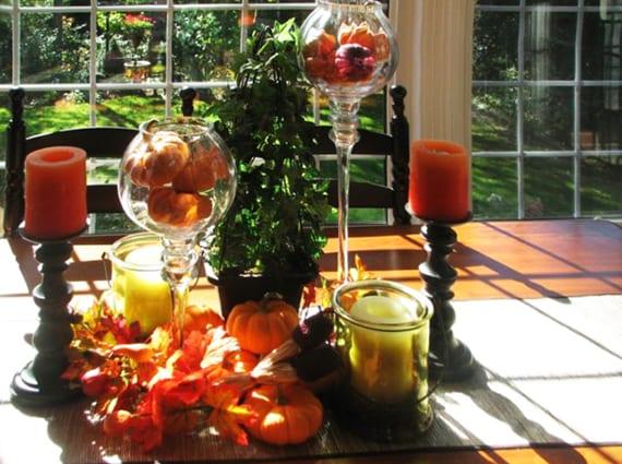 herbstliche tischdeko mit orangen kürbissen in glaswindlichtern, holzkerzenhaltern mit orangen kerzen und windlichtern aus grünem glas