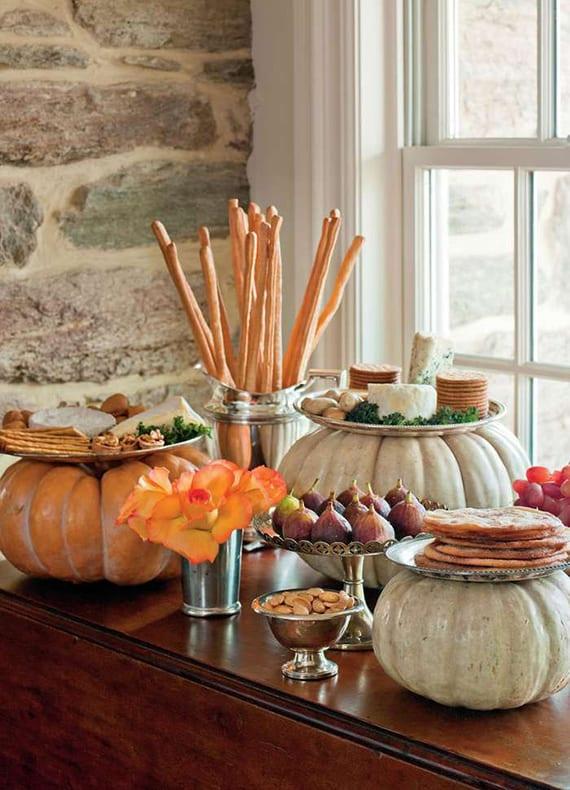 kaltes Bufett aus käsesorten, Nüssen und Herbstfrüchten kreativ arrangiert in silberplatten auf weißen kürbissen