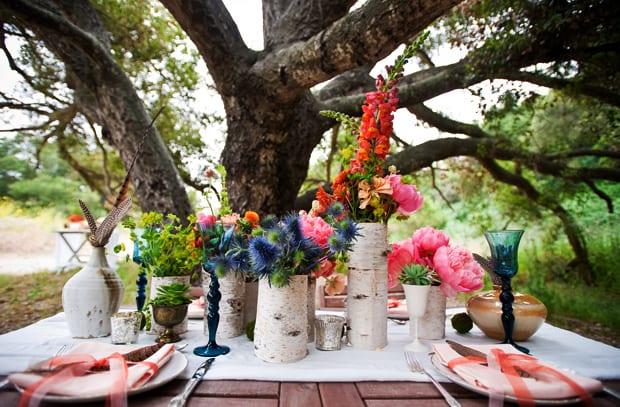 tolle dekoideen für Sommerhochzeit im freien_bunte tischdeko mit blauen weingläsern, frühlingsblumen und diekorativen holzvasen aus birkenholz
