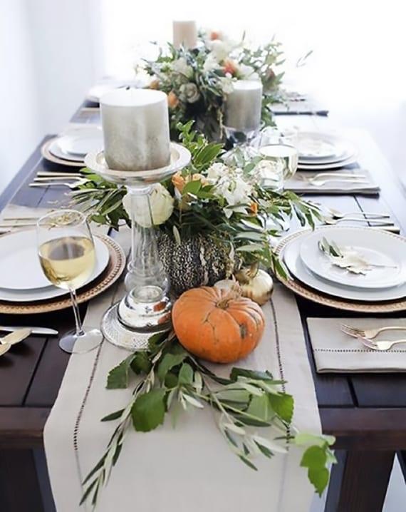 dunkler holztisch elegant decken mit tischläufer beige, goldenen platzteller mit weißen esstellern, glaskerzenhalter mit silbernen kerzen und herbstliche tischdeko mit orangen kürbissen, grünen zweigen und frischen blumen