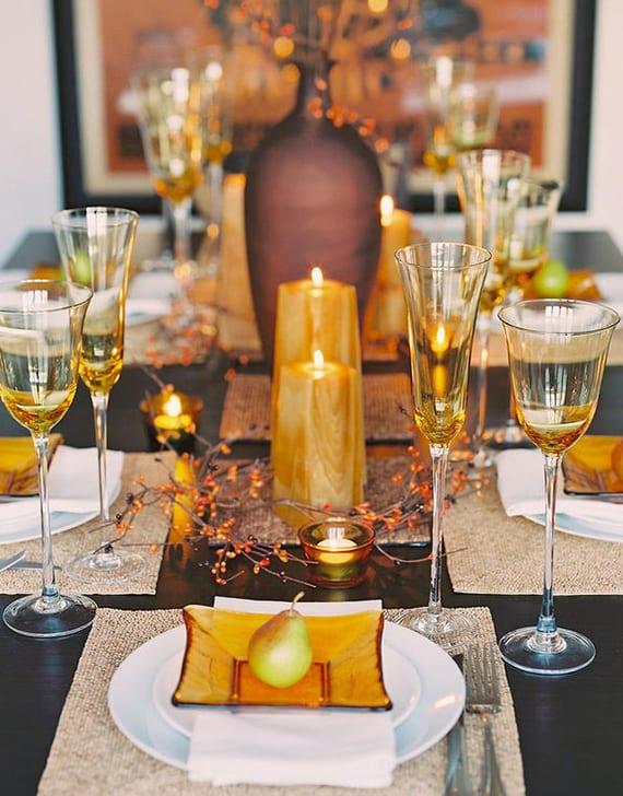 festliche tischdeko Idee für schwarzen esstisch mit goldenen Kerzen, Weingläsern und aus gelbem Glas, gelben Vorspeißetellern mit Birne auf weißen tellern mit weißen stoffservietten