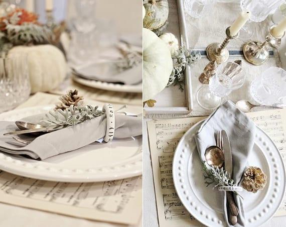 herbstliche tischdeko in weiß mit tischset noten, weißen tellern, kürbisdeko und silber besteck mit weißem servittenring in stoffserviette falten
