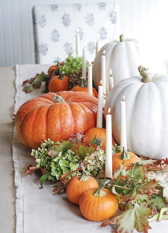 coole dekoideen herbst mit großen weißen kürbissen, kleinen orangen kürbissen, weißen kerzen,baumblättern und hortensie auf rupfen-tischläufer