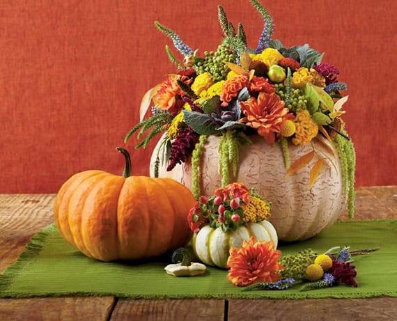 holztisch herbstlich dekorieren mit grünem Platzdeckchen und DIY Vase aus weißem Kürbis mit buntem Strauß aus Herbstblumen