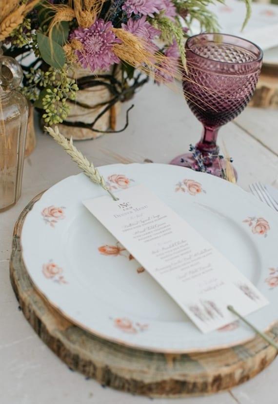 rustikale hochzeit tischdeko mit weißen platztellern auf holzscheiben, lilafarbigen weinglässern, rustikale blumendeko und coole tellerdeko mit Weizenhalm