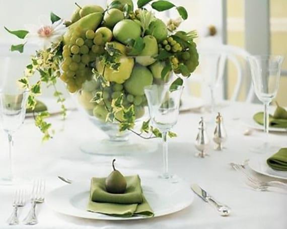 tisch eindecken in weiß mit grünen stoffservieten in weißen tellern und frischer tischdeko mit grünen früchten in glasschale