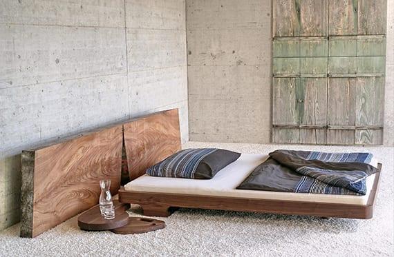 minimalistisches schlafzimmer mit betonwänden, teppichboden weiß, rustikalen holzfensterläden und massivholzbett mit freistehendem bettkopfteil und modernem holznachttisch