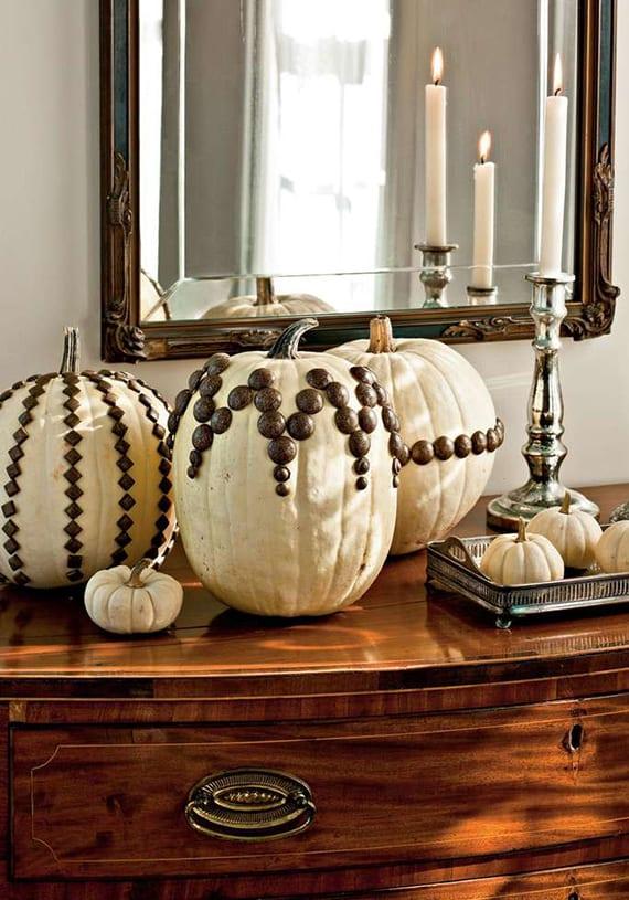 sideboard holz herbstlich dekorieren mit weißen kürbissen und silbernem kerzenhalter vor wandspiegel im antiken spiegelrahmen aus metall