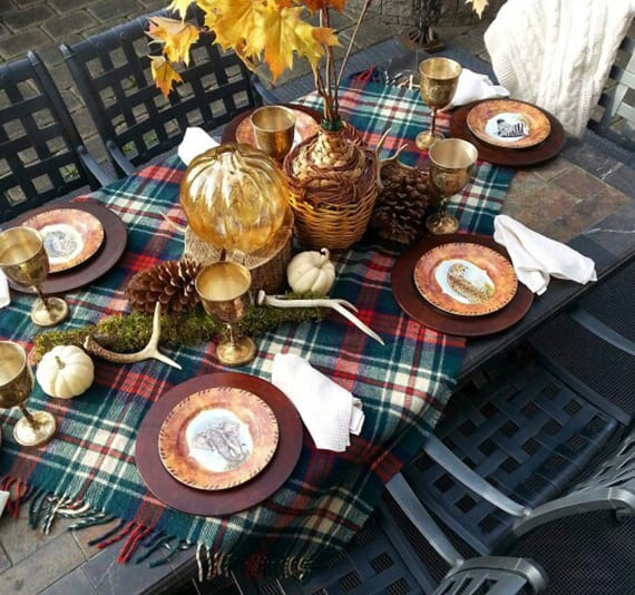 coole tisch herbstdeko für draußen mit blau und rot karierter wolldecke, großen yapfen, weißen Kürbissen, Blätterstraß im Glasballon, silbernen weingläser und braunen platztellern