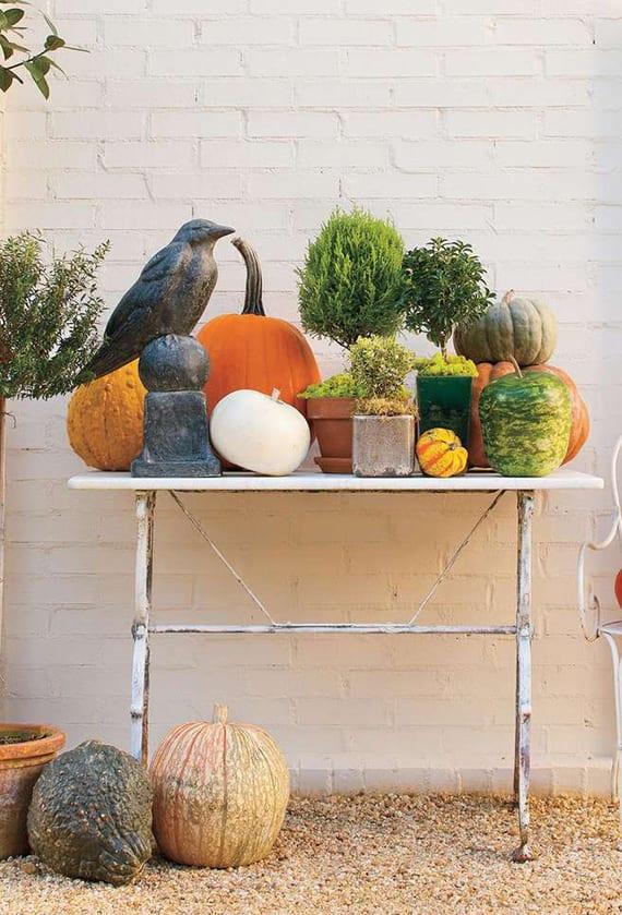 bunte gartendeko idee mit Kürbissen verschiedener Sorten und Farben, kleine Topfbäumen und schwarzer Vogelfigur auf rustikalem Metalltisch weiß