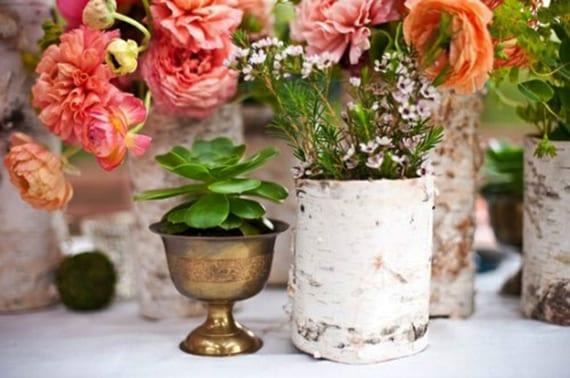 coole frühlingsdeko mit rosafarbigen Ranunkeln in weißen Birkenholzvasen, moosbällen und grünen Saftpflanzen