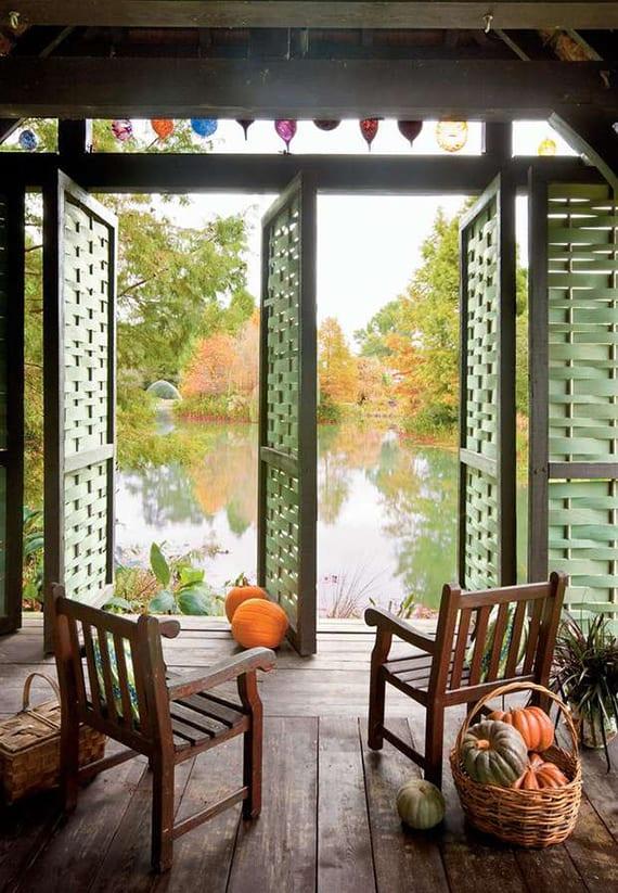 Springhouse mit drehbaren flechtwerk-holztüren im grün und blick auf Teich rustikal dekorieren mit orangen und grünen kürbissen in weidenkörben