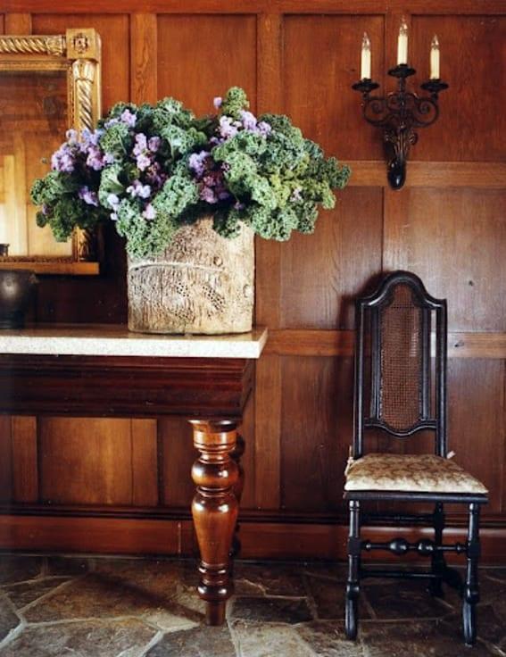 Flur gestaltungsidee mit holzwandverkleidung, steinbodenbelag, kerzenwandlampe und klassischem Sideboard holz mit dekorativer Holzvase aus baumstamm