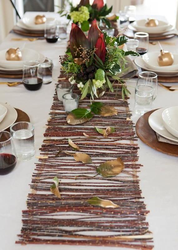 festlich gedeckten tisch herbstlich dekorieren mit diy tischläufer aus zweigen, goldenen grantäpfeln als platztellerdeko und rundem holz tischset