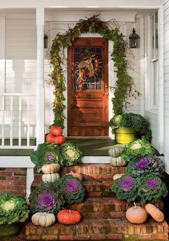 hauseingang herbstlich dekorieren mit weißen kürbissen, grünkohl und Grünschnitt-Girlande aus dem Garten