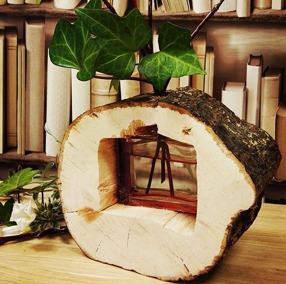 rustikale dekoration mit originelle Vase aus Baumstamm und grünen Blättern
