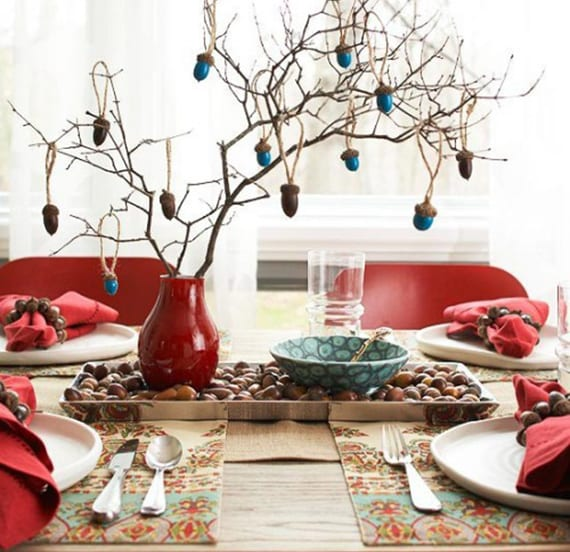 herbstliche tischdeko in rot und blau mit roten stoffservietten, diy serviettenringen aus eicheln, silberne platte mit eicheln, rote vase mit zweigen und blaugefärbten eicheln
