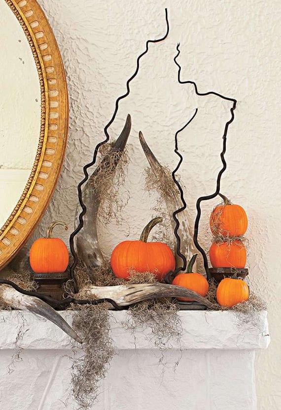 haloween dekoidee für weßen kaminsims mit rundem spiegel im goldrahmen, schwarzen zweigen, orangen kürbissen, moos und Geweihen
