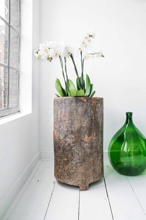 schicke raumgestaltung mit weißem holzfußboden, grüne Glasvase und weißen Orchideen in großer Holzvase rund