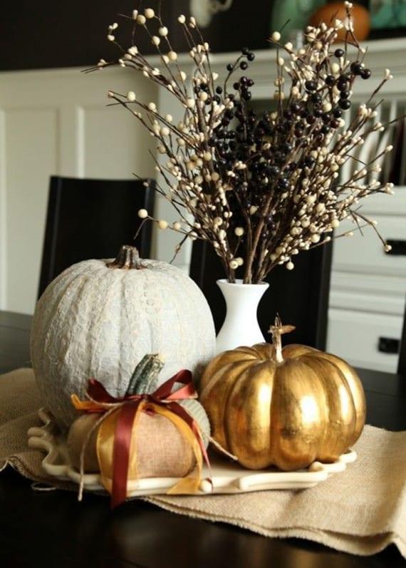 herbstliche tischdeko für schwarzweißes interieur mit künstlichen Kürbissen in weiß und gold, Schneebeeren und Ligusterzweigen in weißer vase