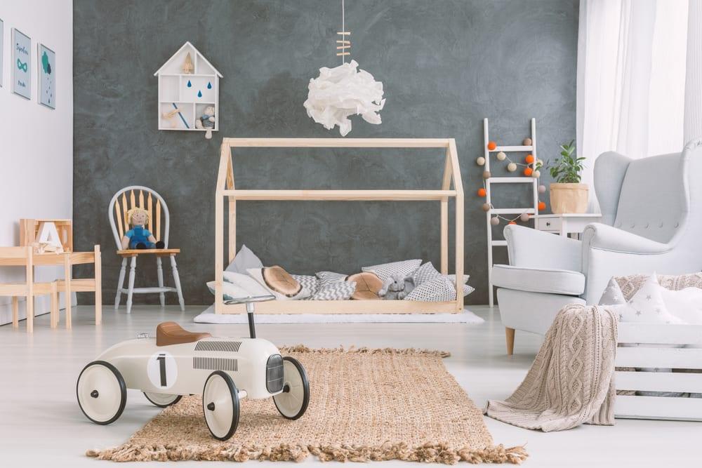 einrichtung minimalistischer kinderzimmer mit holzkindermöbeln, weißem sessel, retro auto, modernem holzbett in hausform, akzentwand grau und weißem bodenbelag