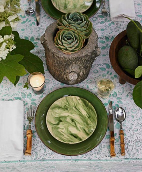 tisch eindecken und dekorieren im rustikeln stil mit grünen tellern, avokadobirnen in holzschale und diy vase aus baumstamm mit saftpflanze