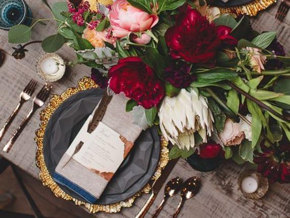 servietten originell falten und tisch herbstlich dekorieren mit Blumen, goldenem besteck und modernen tellern schwarz