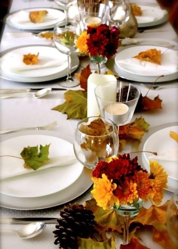herbstliche tischdeko mit grünlichen blättern auf weißen Servietten, Nadelbaumzapfen und herbstblumen in gläsern