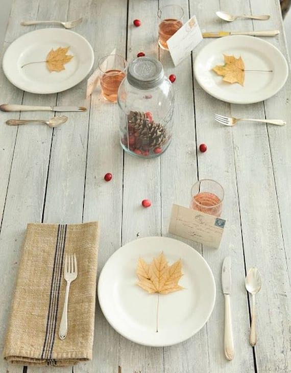 moderne tischdeko herbst für weißen holztisch mit roten moosbeeren, gelben baumblättern in weißen tellern, Rupfen-Servietten und postkarten als tischkarten