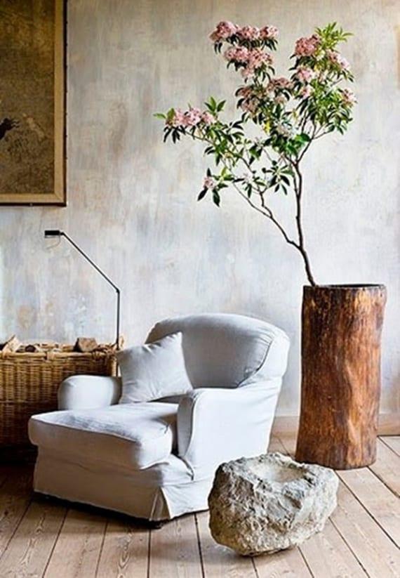 natürliche raumgestaltung mit holzbodenbelag, weißem polstersessel, attraktivem beistelltisch aus weißgrauem felsen und großer Baumstammvase mit blühendem Zweig
