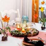 fröhliche tischdeko herbst mit orangen bazmblättern und zwiebelblümen in Einmachgläsern, holzscheibe mit kerzen und orangen tellern mit schwarzen stoffservietten