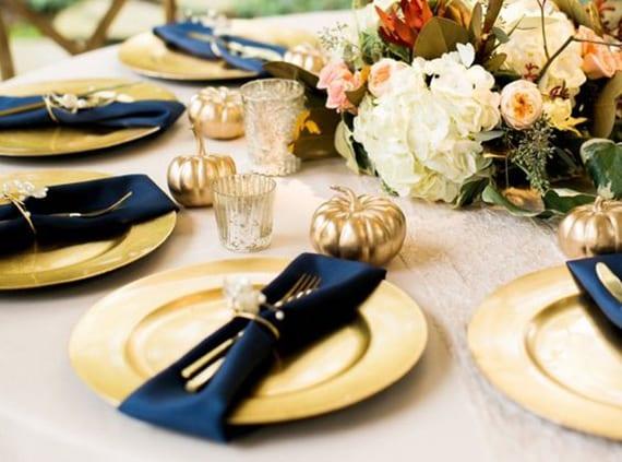 herbstliche tischdeko hochzeit mit goldenen platztellern, schwarzen stoffservietten, goldenen kürbissen und rosen