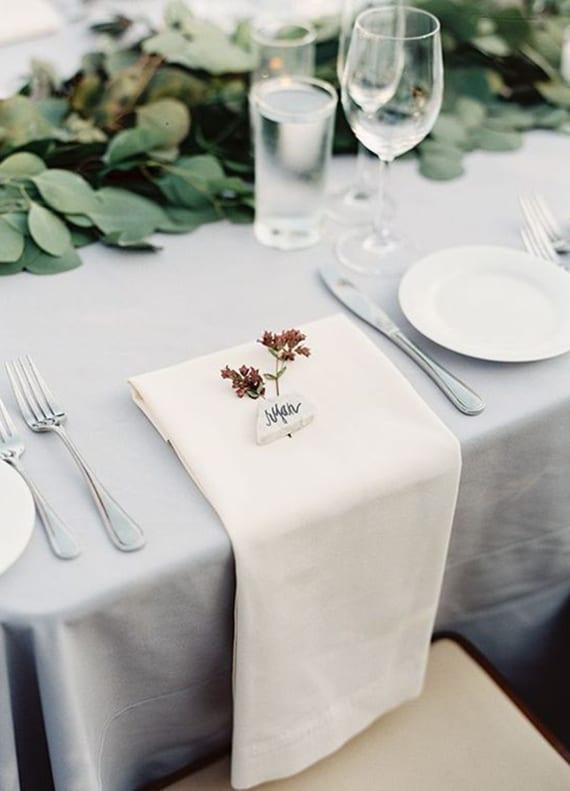 coole hochzeit tischdeko ideen mit grüner blattgirlande und weiße stoffservietten mit diy tischkarte aus stein