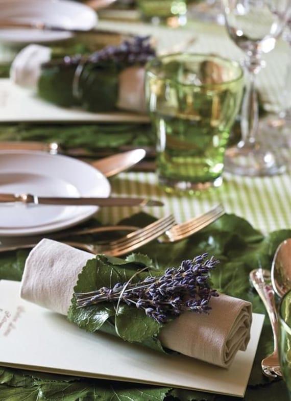 originelle tischdeko mit gestreifter Tischdeke grün, grünen gläsern und menükarte unter gerollten servietten mit blätern