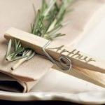 rustikale platzteller dekoidee mit rosmarin,stoffserviette beige und diy tischkarte aus holzwäscheklammer