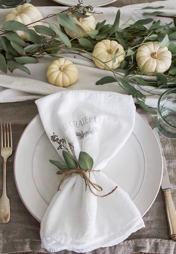 herbstliche tischdeko mit weißen kürbissen und grünen zweigen auf weißer tischdecke