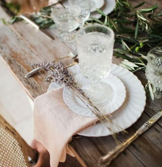 rustikale tischdeko mit olivenzweigen, kristalgläsern, weißen tellern,stoffservieten hellrosa und getrocknetem lavendel