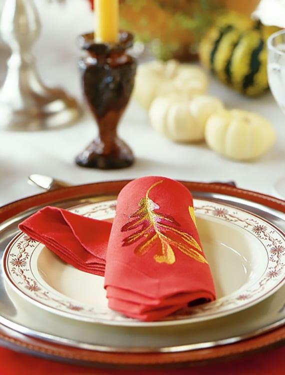 tisch herbstlich eindecken mit weißen kürbissen und roten stoffservietten mit eichelnblatt motiv