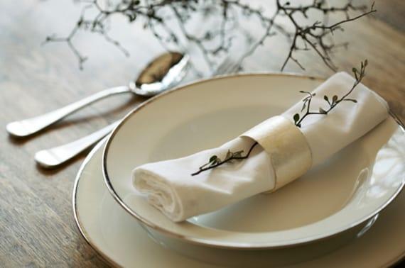weiße stoffservietten falten mit kleinem stängel im weißem servietten ring als moderne platzteller deko