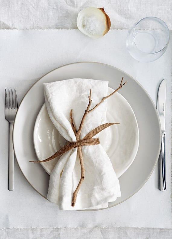 weiße stoffservietten falten mit zweig und stoffband als coole platzteller dekoidee
