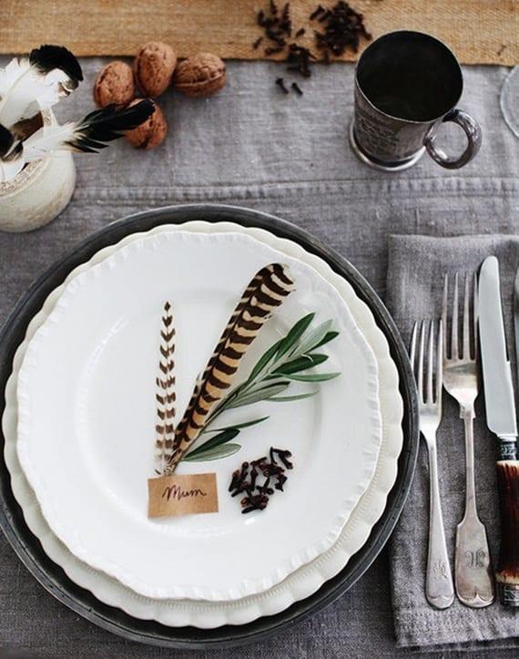 herbstliche tischdeko mit grauer tischdecke, weißen tellernund silbernem Besteck,platzteller aus metall dekorieren mit federn und nelken
