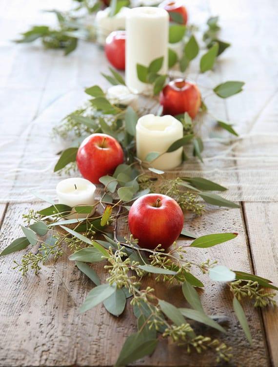 originelle dekoidee für holztische mit grünen zweigen, roten äpfeln und weißen kerzen