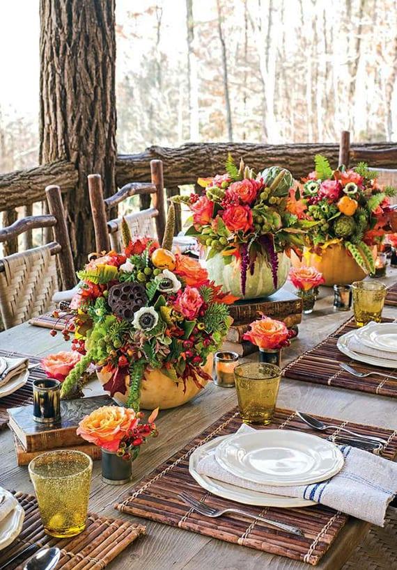 holzesstisch herbstlich dekorieren mit alten büchern, gelben glaswindlichtern, tischset aus holzstäben und drei DIY Kürbisvasen mit blumenstrauß aus rosen, Persimonen,weizen,Hortensien,lotushülsen,farn und eichenlaub