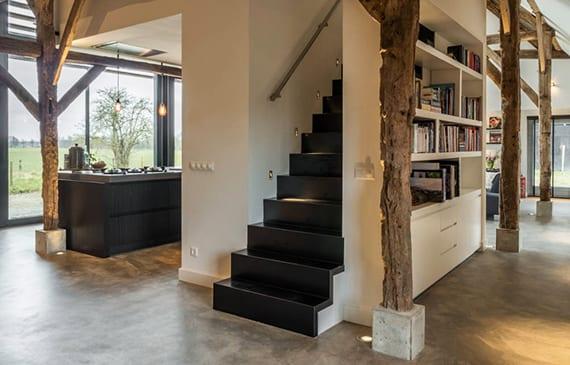 traumhaus mit offenem grundriss und zweitem geschoss kreativ gestalten mit schwarzer stahltreppe, schwarzem kochinsel, weißen wänden und bücherregal, dachstuhl holz und einbaubodenleuchten