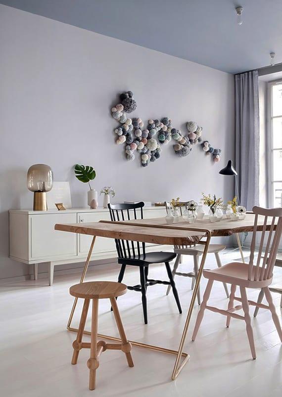 modernes esszimmer frisch gestalten mit wandfarbe helllila, holboden weiß, modernem holesstisch mit metallfüßen, farbigen holzstühlen, und origineller wanddeko mit pom-poms in pastellfarben