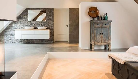 einrichtungsideen schlafzimmer mit offenem badezimmer, podest mit grauen bodenfliesen, doppelwaschtischschrank weiß, antike holzmöbeln und wandgestaltung mit wandfarbe grau und grauer steinmosaik
